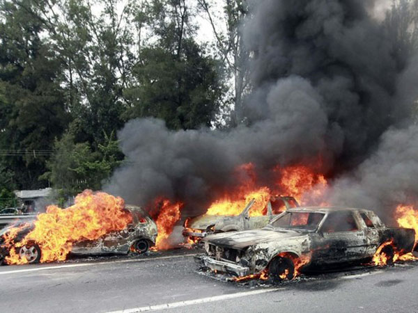 Burning vehicles used as roadblocks are seen on the outskirts of Guadalajara